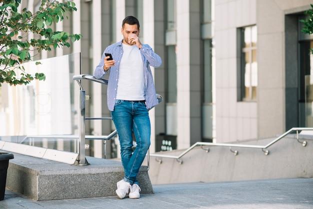 Homem bebendo café perto do corrimão