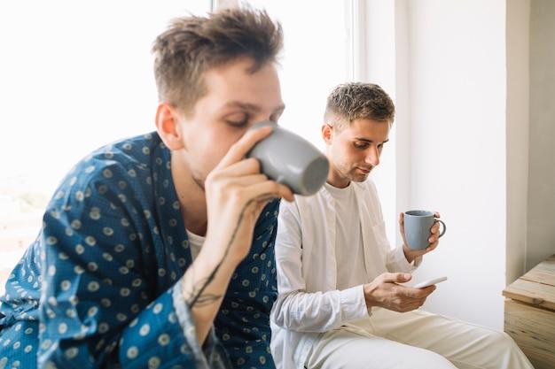 Homem, bebendo, café, sentando, perto, seu, amigo, usando, smartphone