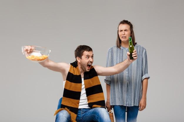 Homem bebendo cerveja, assistindo futebol, chateado mulher em pé atrás, chorando
