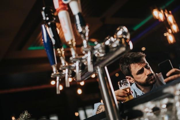 Homem bebendo cerveja e fumando cigarro no pub na boate