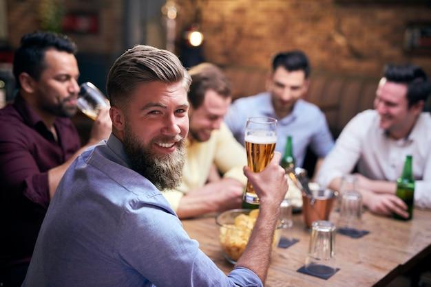 Homem bebendo cerveja em bar e amigos