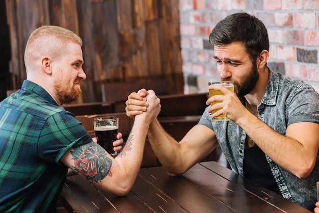 Homem, bebendo, cerveja, enquanto, braço wrestling, com, seu, amigo