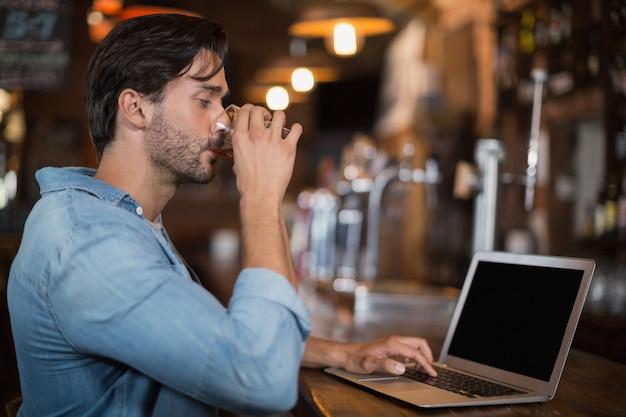 Homem bebendo cerveja enquanto estiver usando o laptop em restarant