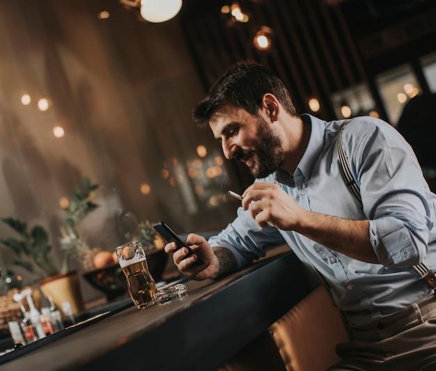 Homem bebendo cerveja, fumando cigarro e olhando para o celular no pub