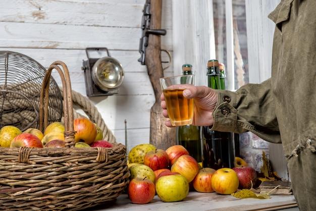 Homem bebendo copo de cidra, garrafa e maçãs orgânicas