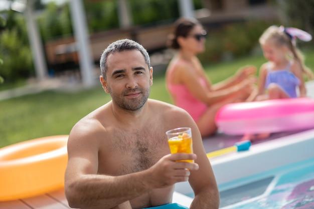 Homem bebendo coquetel. homem barbudo de olhos escuros bebendo coquetel gelado enquanto relaxa com a família perto da piscina
