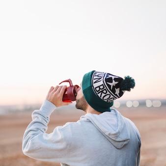 Homem bebendo de termos na natureza