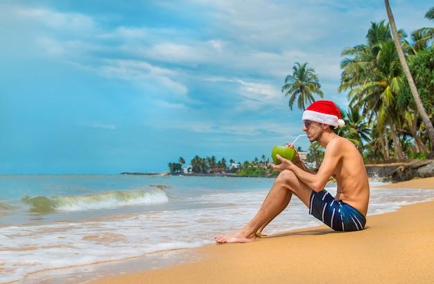 Homem bebendo um coquetel com chapéu de papai noel na praia