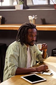 Homem bebendo uma xícara de café