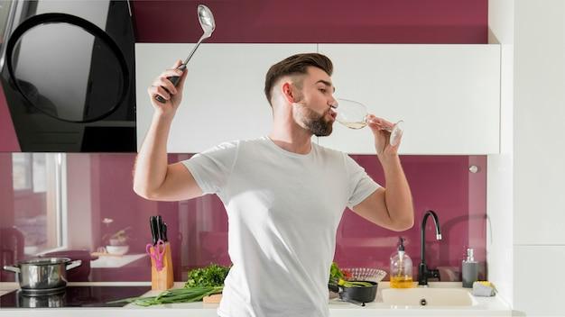 Homem bebendo vinho e brincando na cozinha tiro médio