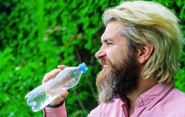 Homem beber água ao ar livre. macho barbudo com garrafa de água. estilo de vida saudável. água potável.