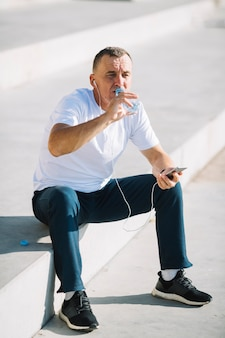 Homem beber água de garrafa de plástico