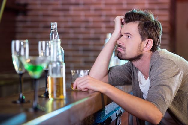 Homem bebido novo que bebe o álcool na barra.