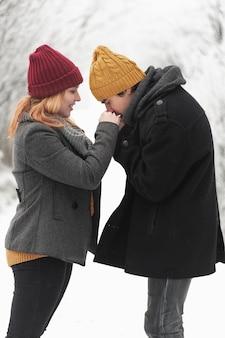 Homem beijando as mãos da namorada plano médio