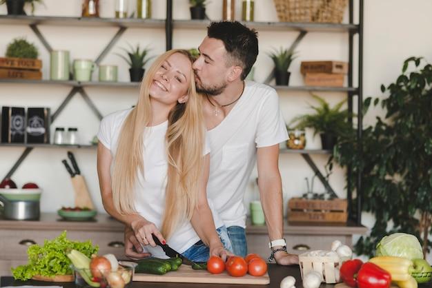 Homem, beijando, dela, namorada, legumes cortantes, em, cozinha