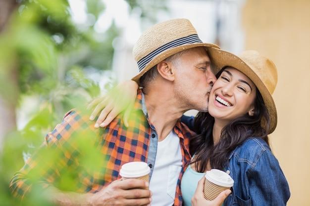 Homem beijando mulher alegre com café