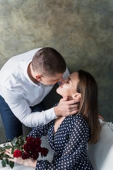 Homem, beijando, mulher, com, flores