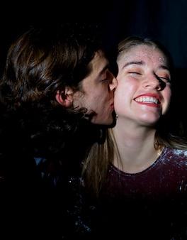 Homem, beijando, mulher, com, lantejoulas, ligado, rosto