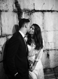 Homem, beijando, mulher, inclinar-se, predios, parede