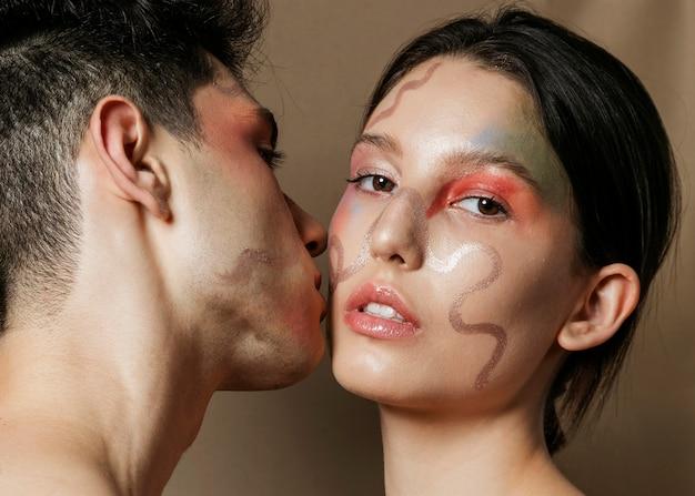 Homem beijando mulher na bochecha com rostos pintados