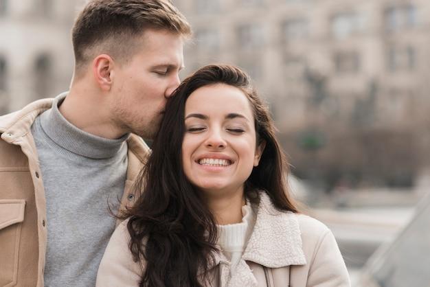 Homem beijando mulher na cabeça do lado de fora
