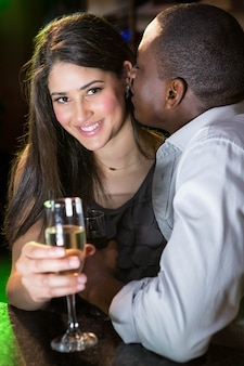 Homem beijando mulher no balcão de bar em bar