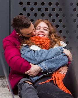 Homem beijando namorada feliz vista frontal