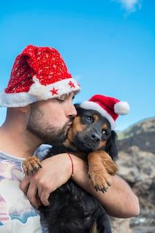 Homem beijando seu cachorro no natal usando chapéus de natal