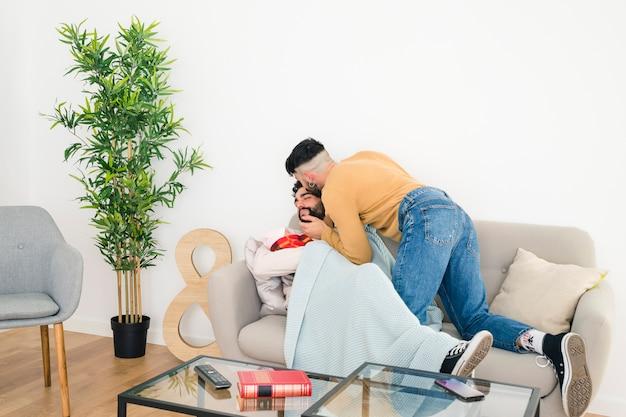 Homem beijando seu namorado deitado no sofá com o bebê na mão em casa