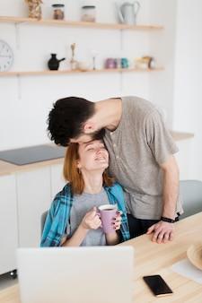 Homem beijando sua namorada na testa, vista alta