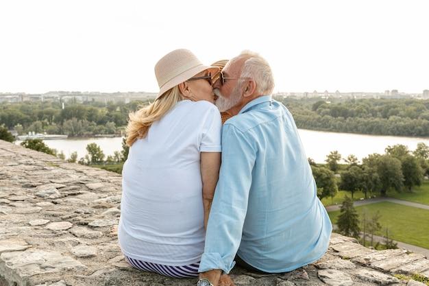 Homem beijando uma mulher sob um chapéu