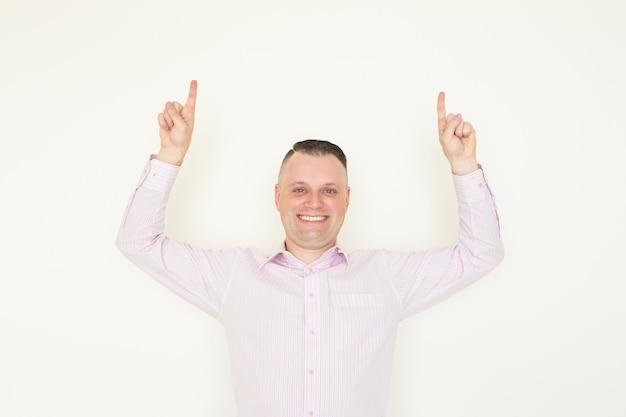 Homem bem sucedido alegre que mostra os dedos acima e olhando a câmera.