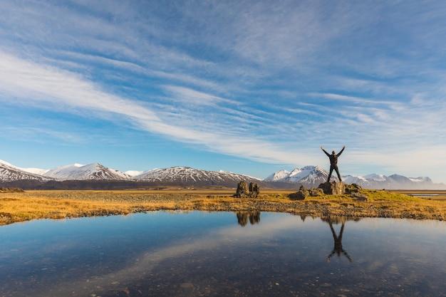 Homem bem sucedido na islândia com seu reflexo na água