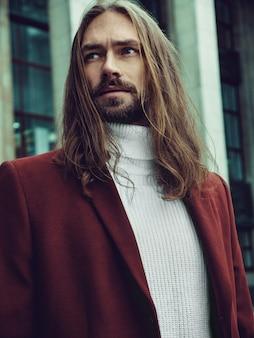 Homem bem vestido confiante bonito com barba posando ao ar livre, olhando para longe. elegante modelo masculino rico em casaco de inverno vermelho e camisola branca
