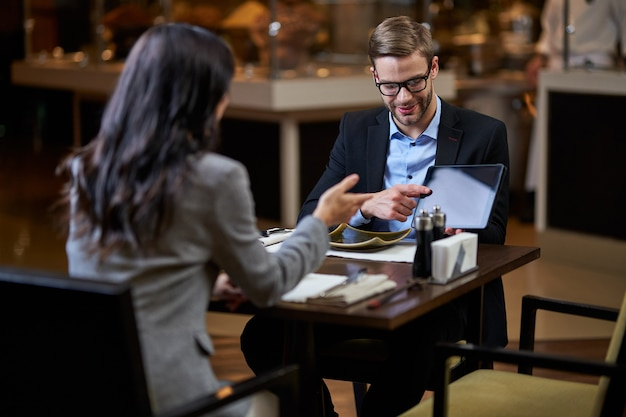 Homem bem vestido inclinando a cabeça para baixo enquanto mostra a tela do tablet com o dedo para uma empresária falando diante dele