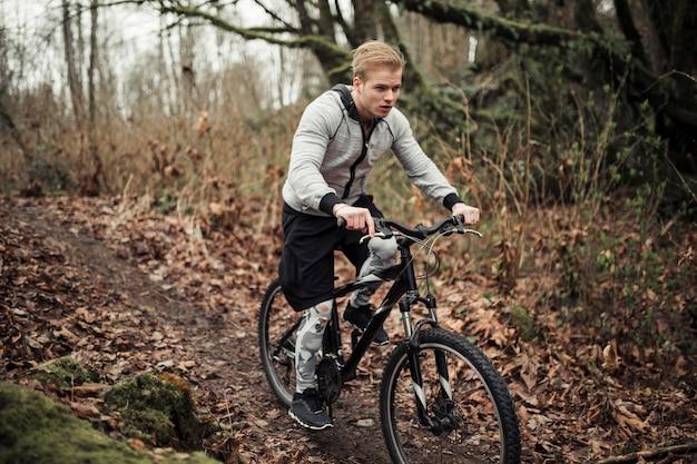 Homem, bicicleta equitação, em, a, floresta, durante, outono