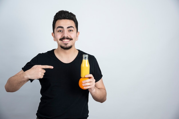 Homem bigodudo, apontando para a fruta laranja com uma garrafa de vidro de suco.