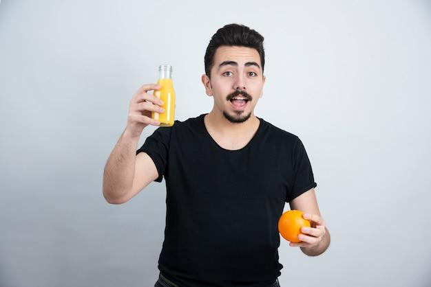 Homem bigodudo segurando uma fruta laranja com uma garrafa de vidro de suco.