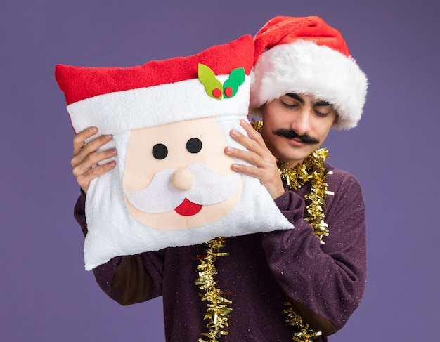 Homem bigodudo usando chapéu de papai noel de natal com enfeites em volta do pescoço segurando uma almofada de natal com os olhos fechados, feliz e positivo em pé sobre a parede roxa