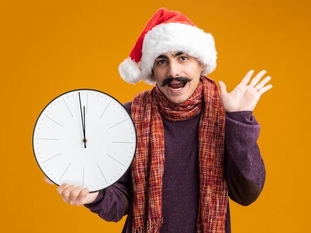 Homem bigodudo usando chapéu de papai noel de natal com lenço quente em volta do pescoço segurando um relógio feliz e animado em pé sobre uma parede laranja