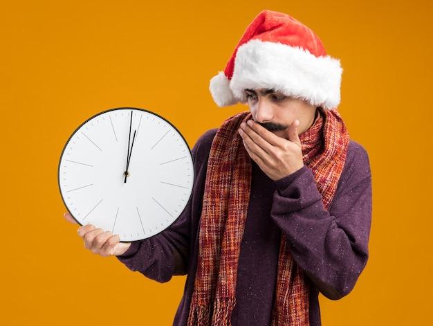 Homem bigodudo usando chapéu de papai noel de natal com um lenço quente em volta do pescoço segurando um relógio olhando para ele, espantado, cobrindo a boca com a mão em pé sobre a parede laranja