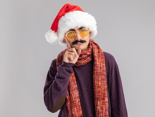 Homem bigodudo usando chapéu de papai noel de natal e óculos amarelos com um cachecol quente no pescoço parecendo perplexo