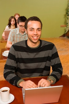 Homem biracial na cabeça da linha de usuários de laptop