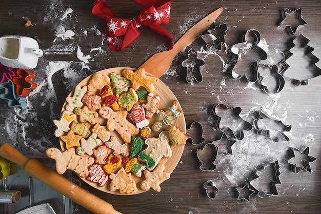 Homem-biscoito assado, biscoitos em formas diferentes mentem em uma bandeja de madeira. o conceito de tradições de ano novo e o processo de cozimento. cookies em uma mesa de madeira marrom. produção familiar. padaria caseira