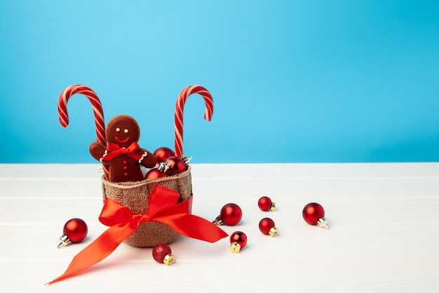 Homem-biscoito e bastões de doces em uma cesta contra o azul