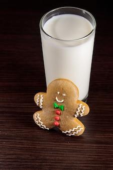 Homem-biscoito e copo de leite na mesa de madeira escura. conceito de natal