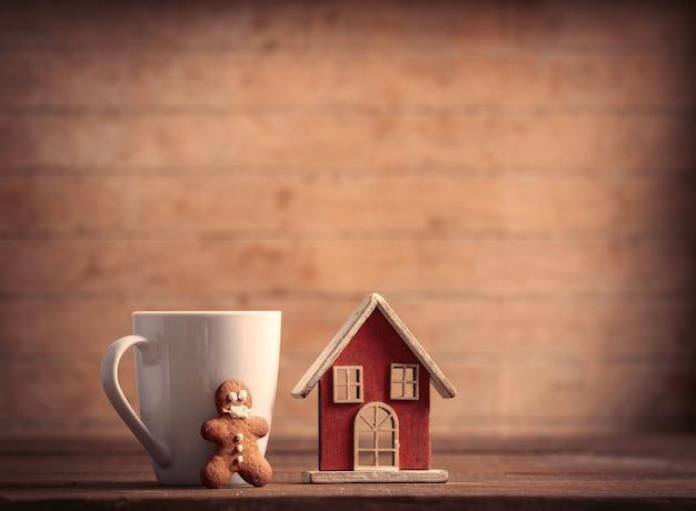 Homem-biscoito na máscara e copo com casa de brinquedo em uma mesa de madeira