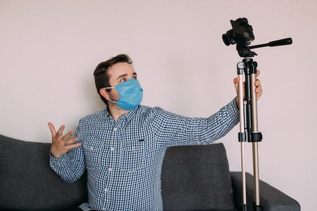 Homem blogueiro em máscara médica fala sobre coronavírus. o blog de gravação de vídeos do homem diz como se proteger de 2019-ncov. blogger fala mers-cov como usar lenços de álcool, termômetro