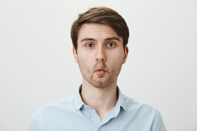 Homem bobo brincalhão com lábios de peixe imitando