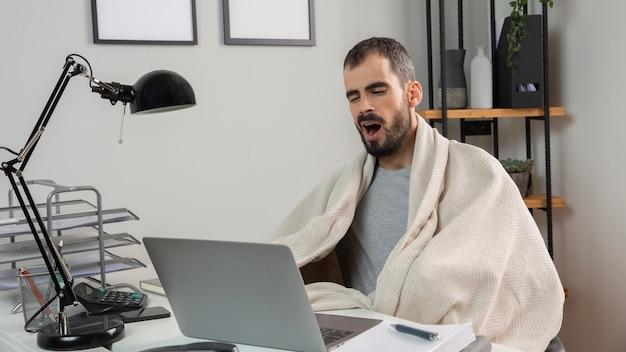 Homem bocejando enquanto trabalha em casa